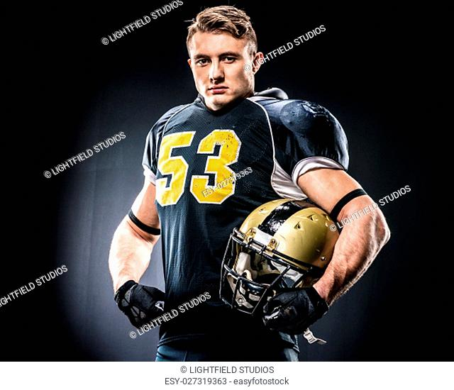 American football player holding helmet and looking at camera on black