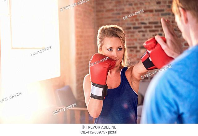 Young female boxer practicing boxing with trainer in gym studio
