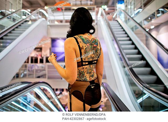 A model with tattoos on her back and wearing lingerie from a collection designed by Burlesque model Dita von Teese stands in front of escalators of a newly...