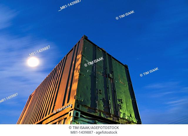Steel shipping container and moon  Sidney, Vancouver Island, British Columbia, Canada