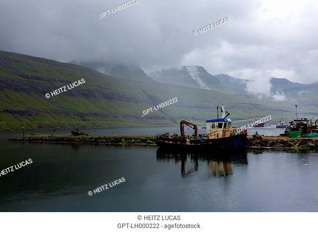 OLD RUSTED FISHING BOAT IN RAINY WEATHER SURROUNDED BY MOUNTAINS IN A FJORD, FUNNINGSFJORDUR, EYSTUROY, FAROE ISLANDS, DENMARK