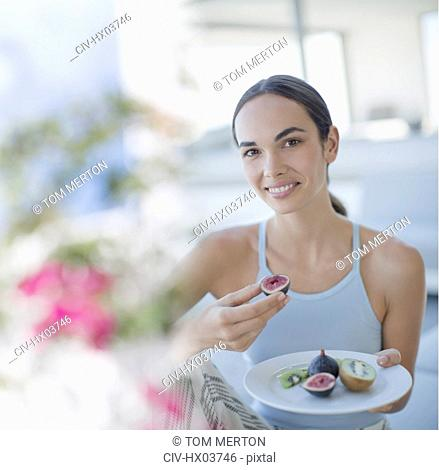 Portrait smiling brunette woman eating figs and kiwi