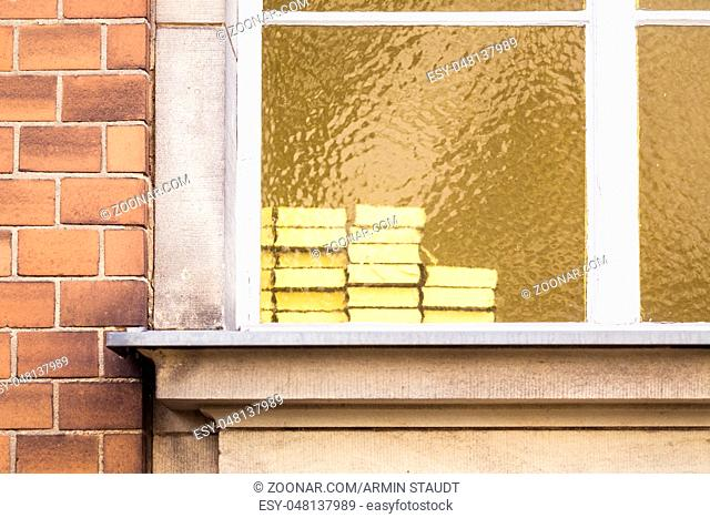 pile of books behind a yellow window