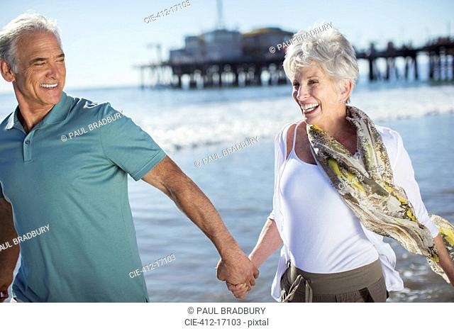 Enthusiastic senior couple running on beach