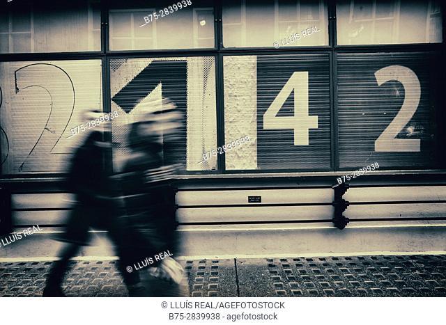 Dos personas andando en movimiento irreconociles, al fondo una fachada con numeros 2-1-4-2. London, UK, Europa