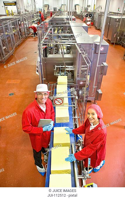 High angle view portrait smiling quality control workers at production line in cheese processing plant