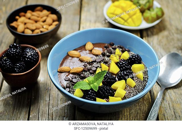 A breakfast bowl with chocolate smoothie, mango, blackberries, chia seeds, chocolate chips and almonds