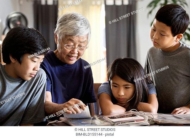 Asian grandmother and grandchildren looking at photo album