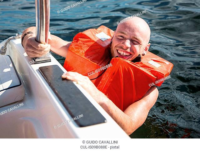 Man wearing lifejacket in water looking at camera smiling