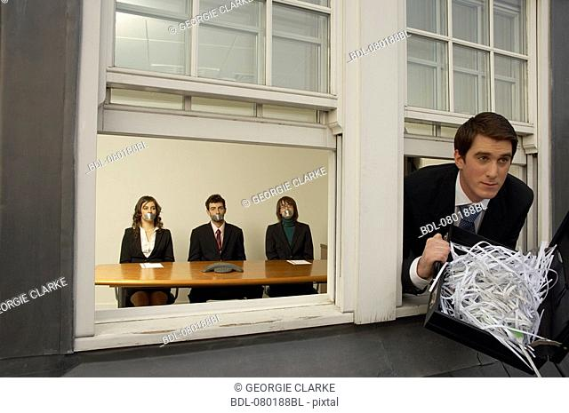 businessman leaving office building through window with briefcase full of shredded paper