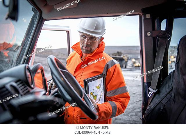 Geologist holding digital tablet in truck in surface coal mine