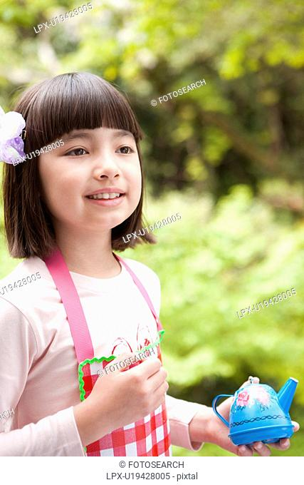 Young Girl Holding Toy Teapot