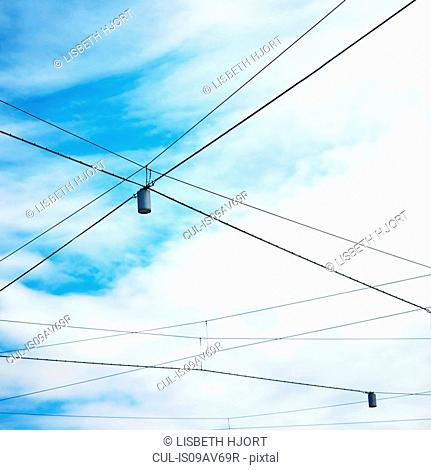 Low angle view of blue sky and street lights with criss crossed wires