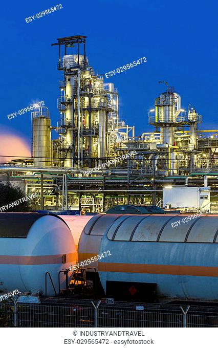 A chemical plant and refinery with night blue sky and illumination, some freight trains in the foreground