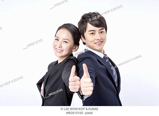 Portrait of smiling business people showing thumbs-up