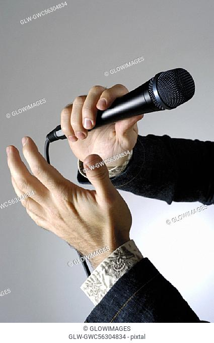 Close-up of a man's hand holding a microphone