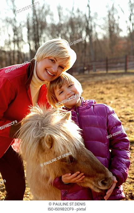 Portrait of mother and daughter outdoors, standing with pony