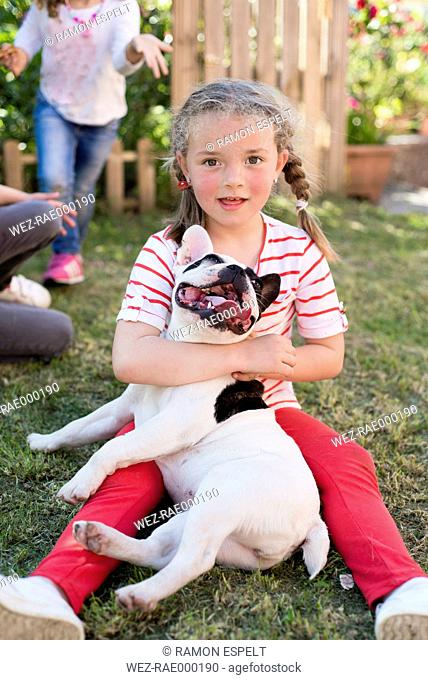 Portrait of little blond girl with her French bulldog