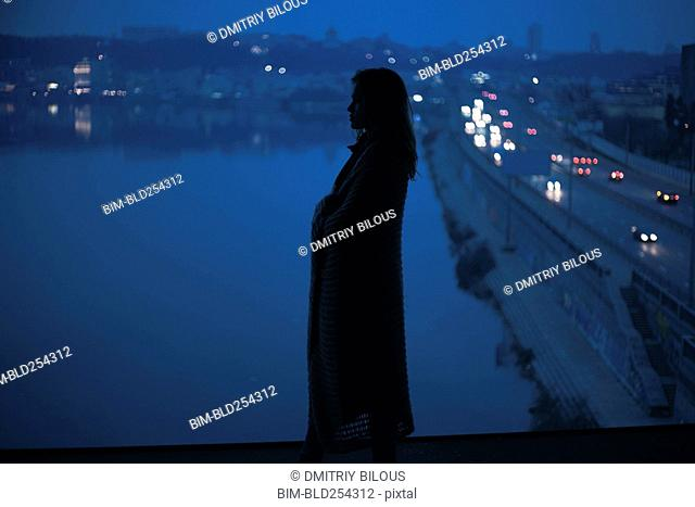 Caucasian woman standing near waterfront at night