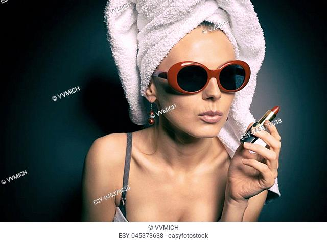 actress after a shower in a towel on her head and fashionable sunglasses chooses a lipstick color looking in the mirror