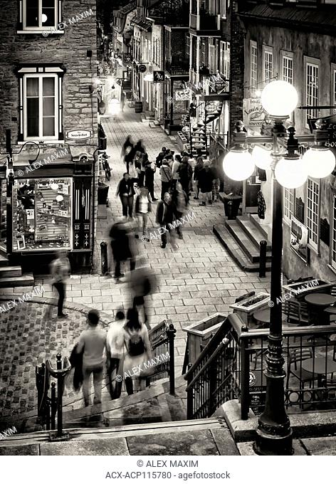 People walking at night on historic streets Rue du Petit Champlain and Rue Sous Le Fort of old Quebec City, view from above. Quebec, Canada