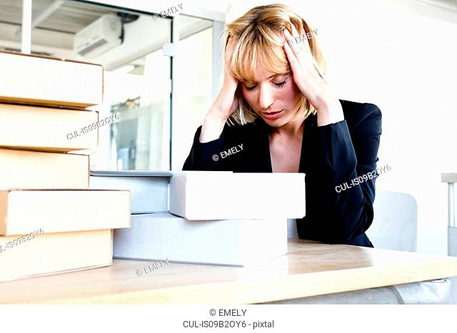 Business woman with stack of books, head in hands looking stressed