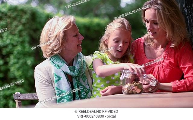 Girl filling coin jar with grandmother and mother