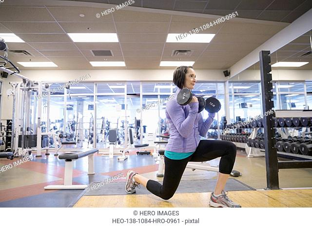 Woman weight lifting at gym