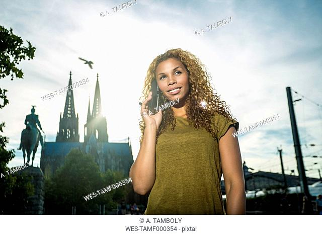 Germany, Cologne, portrait of relaxed young woman at backlight