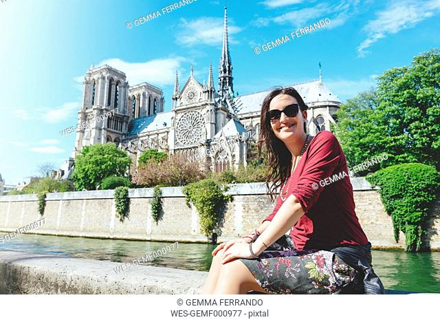 France, Paris, smiling woman sitting on the bank of the Seine river in front of Notre-Dame de Paris