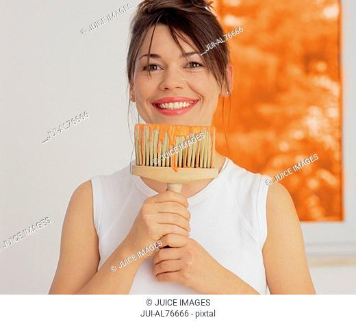 Portrait of a young woman holding a paint brush