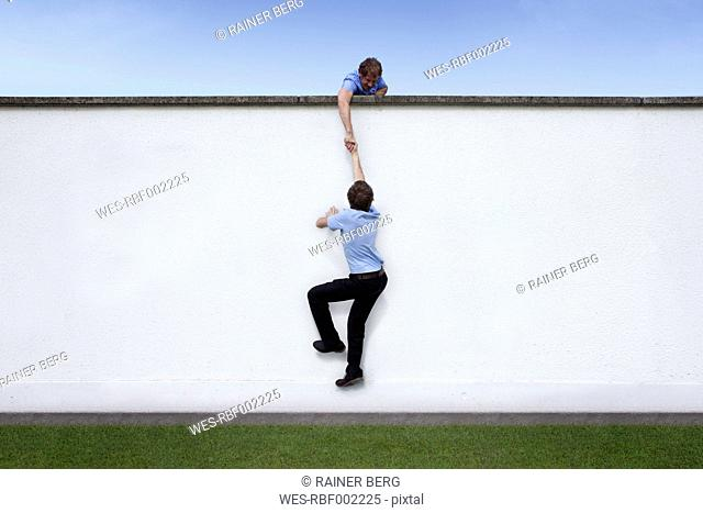 Business man helping colleague on wall