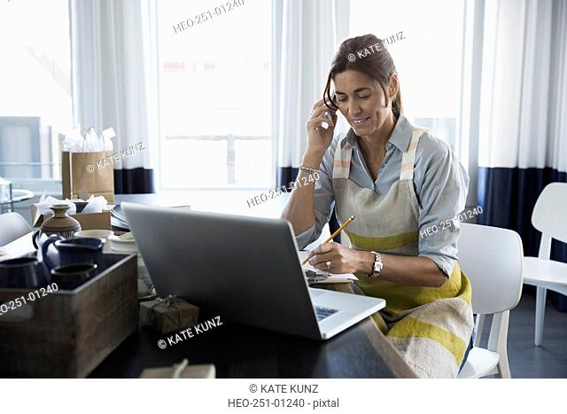Woman with pottery working laptop talking cell phone