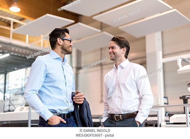 Two smiling businessmen talking in modern factory