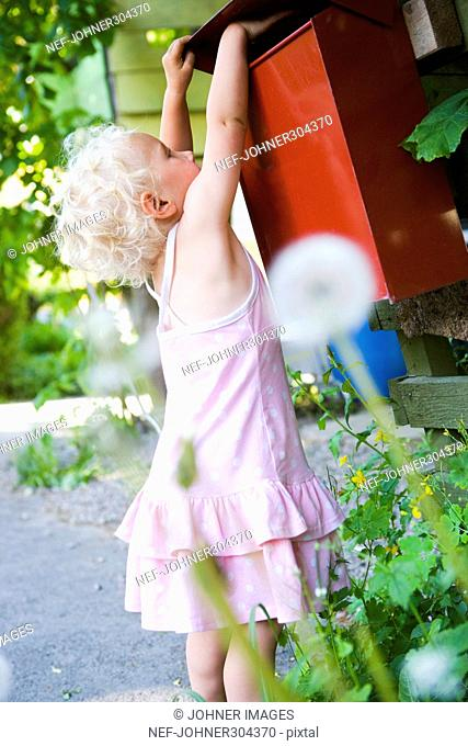 A girl getting mail from a mail box