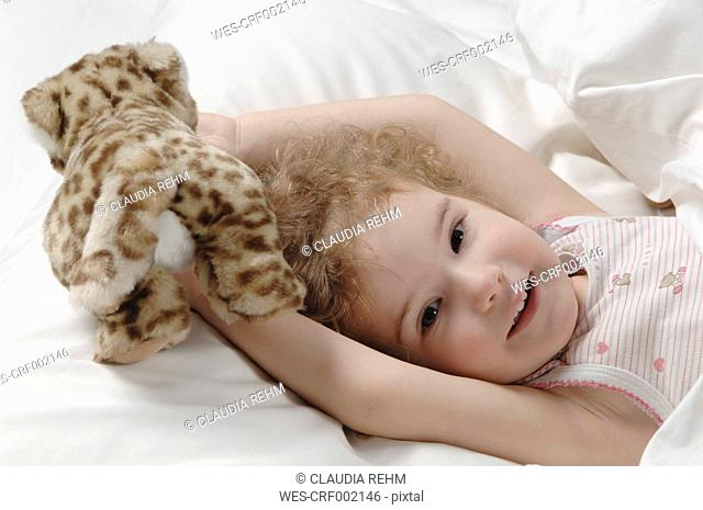 Girl lying on bed with toy, smiling