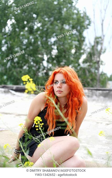 pretty redhead girl outdoors in ruin