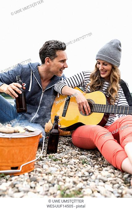 Happy couple with beer bottles, guitar and grill relaxing on pebble beach