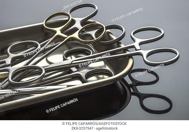 Some scissors for surgery on a tray, conceptual image, horizontal composition
