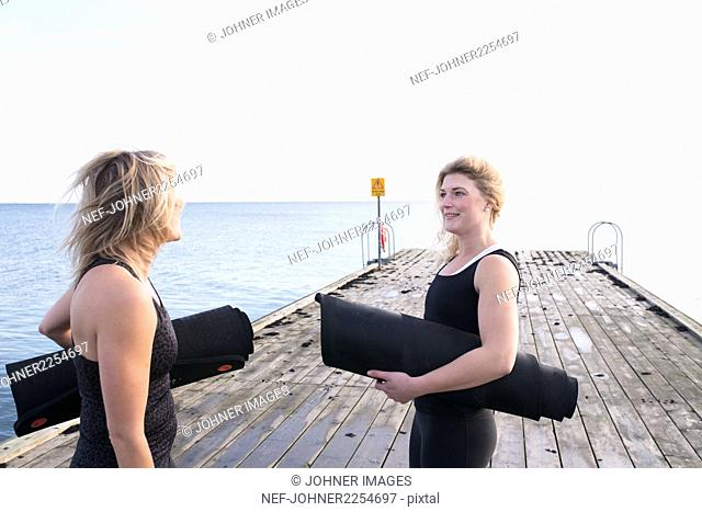 Two women holding exercise mats, talking on pier