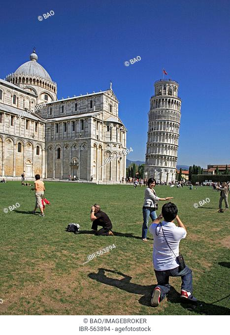 Tourist taking pictures of the cathedral Santa Maria Assunta and the Leaning tower, Pisa, Tuscany, Italy
