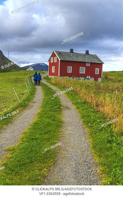 People walking on path towards a traditional house, Flakstad, Nordland county, Lofoten Islands, Norway
