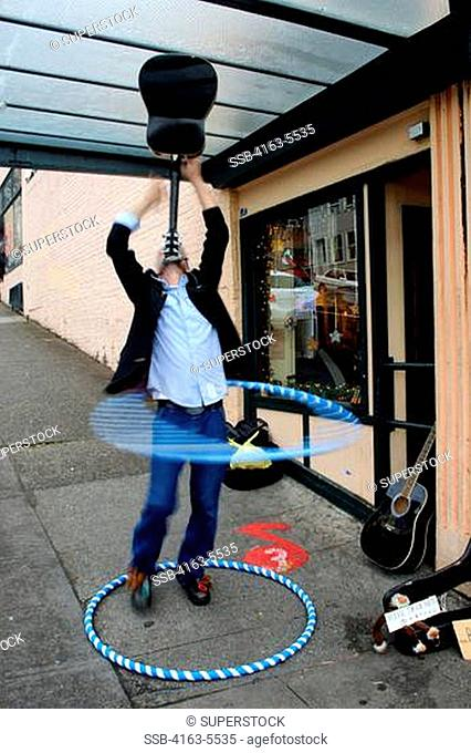 USA, WASHINGTON STATE, SEATTLE, PIKE PLACE MARKET, STREET PERFOMER WITH GUITAR AND HULA HOPS