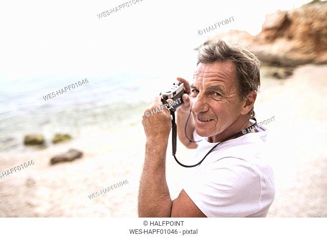 Portrait of senior man taking pictures on the beach