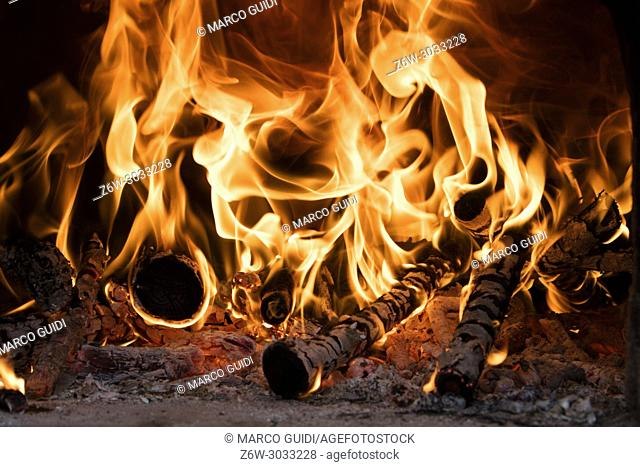 Fire and flame produced by burning wood inside an oven