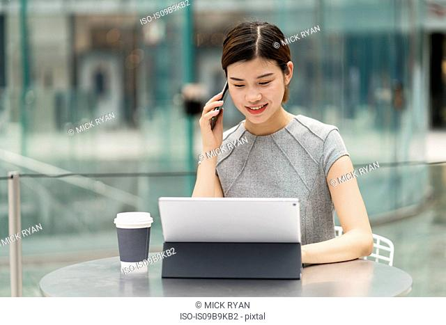 Young city businesswoman making smartphone call from sidewalk cafe