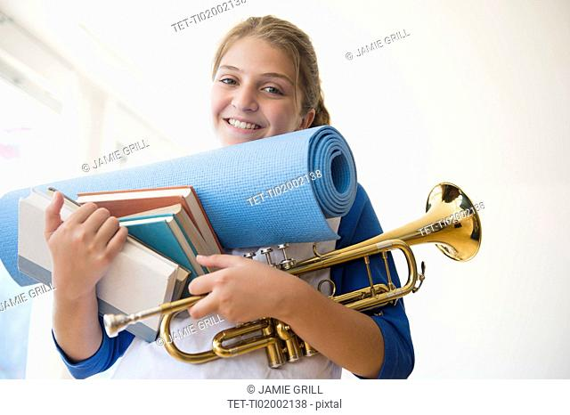 Portrait of teenage girl (12-13) holding rolled-up exercise mat, books, and trumpet