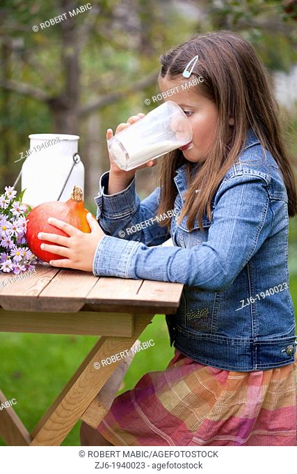Girl drinking a glass of milk outdoor in the garden. Slovenian countryside