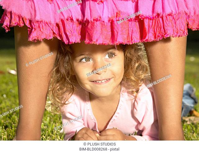 Young girl looking through mother's legs