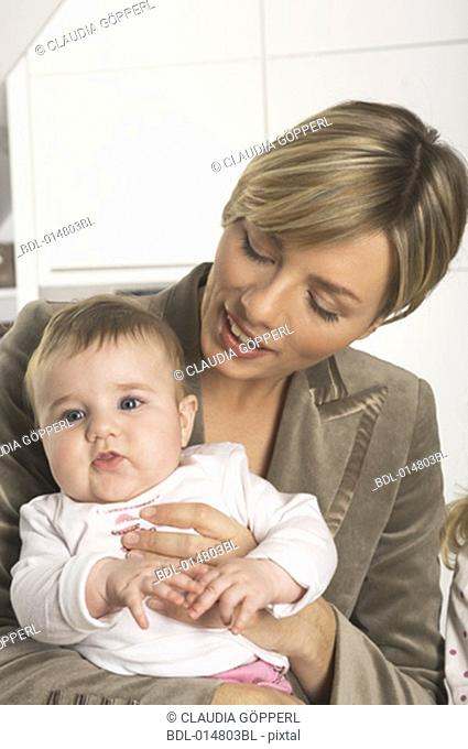portrait of young businesswoman holding her little baby daughter